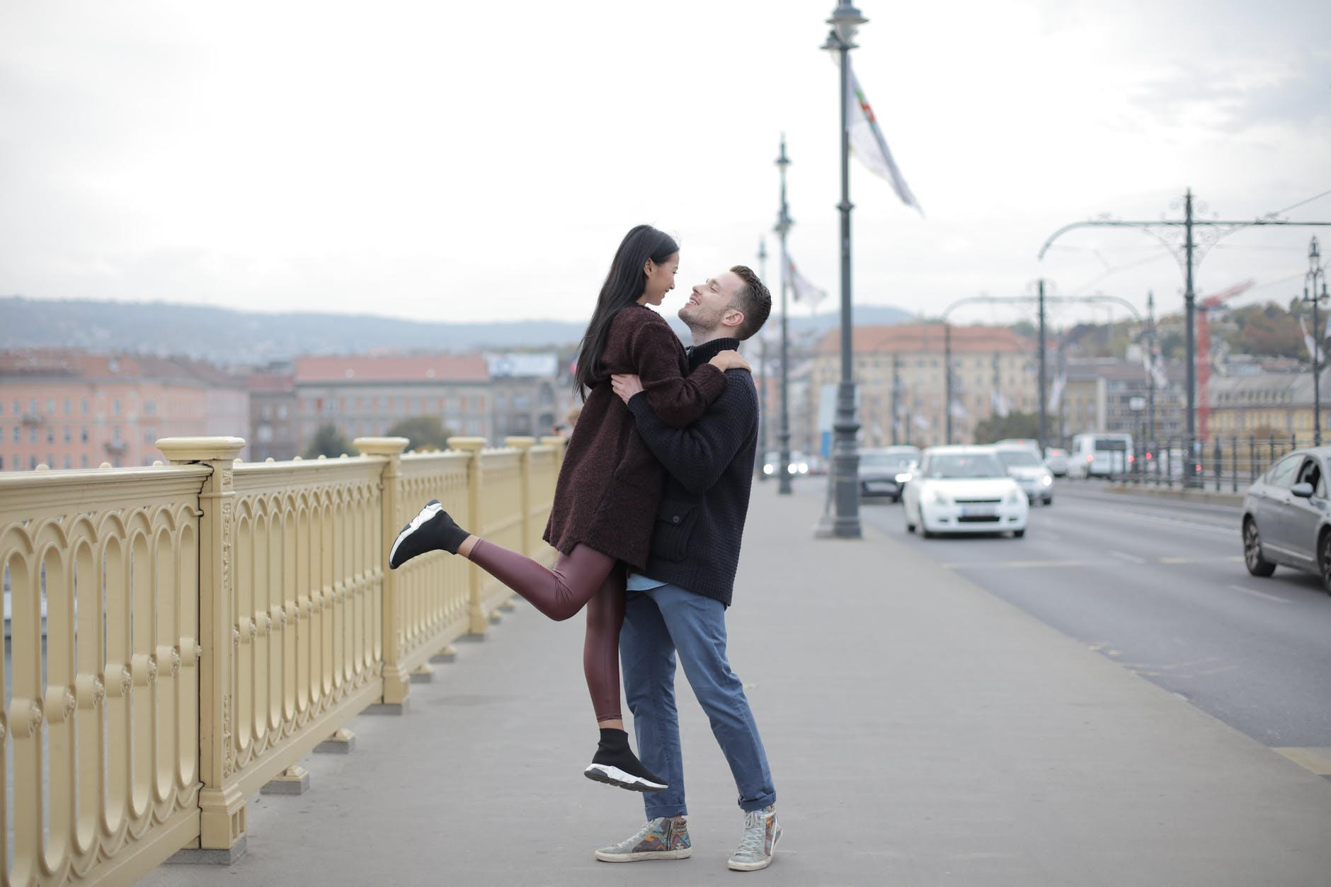 positive young multiracial couple hugging on bridge during walk on street in city